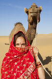 Woman holding a camel in the desert. Stock Photography