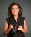 Woman holding a camera. Portrait of a woman holding a photographic camera Stock Image