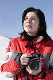 Woman holding a camera. Attractive woman in sport wear holding a camera, winter outdoors Stock Image