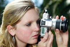 Woman holding camera. Young woman holding silver camera Stock Photo