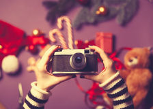 Woman holding a camera. On christmas gifts background Stock Photo