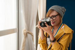 Woman holding the camera. Indoor portrait of Asian pretty woman holding the camera in a house, hipster style, eyeglasses and hat Stock Images