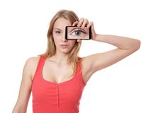Woman holding camera phone to her face. Young woman holding camera phone in front of face showing enlarged eye Stock Images