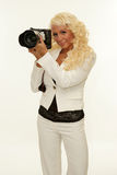 Woman holding camera. Picture of mature blond woman holding camera with zoom Royalty Free Stock Photo