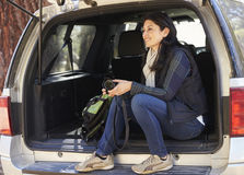 Woman holding camera sits in the open back of a car Stock Photography