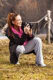 Woman holding camera and taking photo outside. Young woman holding camera and taking photo outside Royalty Free Stock Photography