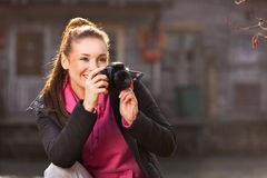 Woman holding camera and taking photo outside. Young woman holding camera and taking photo outside Royalty Free Stock Image