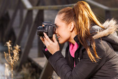 Woman holding camera and taking photo outside Royalty Free Stock Photography