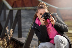 Woman holding camera and taking photo outside Royalty Free Stock Photo