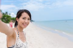 Woman holding camera to take selfie in beach Royalty Free Stock Images