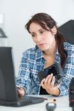 Woman holding camera and typing into laptop Stock Image