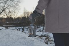Woman holding candle lantern in winter forest. royalty free stock photography
