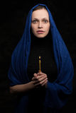 Woman holding candle and praying Stock Photo