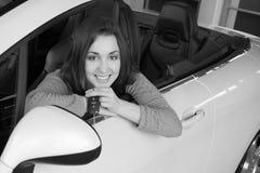 Woman holding car key inside car dealership Stock Photo