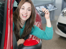 Woman holding car key inside car dealership Royalty Free Stock Image