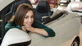 Woman holding car key inside car dealership Royalty Free Stock Photo