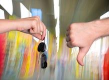 Woman holding car key, man showing thumb down Royalty Free Stock Photography