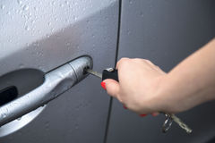 Woman holding car key and opening door. Royalty Free Stock Photos