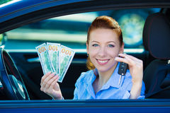 Woman holding car keys, dollar bills, sitting in her new car Royalty Free Stock Photo