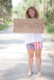 Woman holding card. Pretty young woman holding happiness card Royalty Free Stock Images