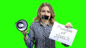 Woman holding card with inscription Freedom of speech. Young speechless woman with adhesive tape on mouth trying to speak in megaphone. Alpha Channel stock video