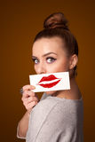 woman holding card with kiss lipstick mark on gradient background Royalty Free Stock Photography