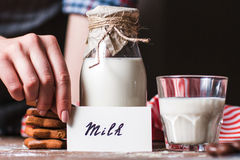 Woman holding card near bottle of milk royalty free stock image