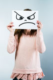 Woman holding a cardboard with a angry face. Young woman holding a cardboard with a angry face on it in front of her head Stock Photos