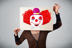 Woman holding a cardboard with a clown on it in front of her hea Stock Photography