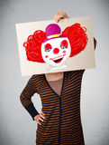 Woman holding a cardboard with a clown on it in front of her hea Stock Images