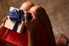 Woman holding a cardboard gift box with blue ribbon Stock Photo
