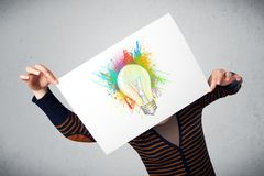 Woman holding a cardboard with paint splashes and lightbulb in f Stock Photo