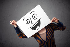 Woman holding a cardboard with smiley face on it in front of her Stock Image