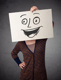 Woman holding a cardboard with smiley face on it in front of her Royalty Free Stock Photos