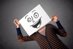 Woman holding a cardboard with smiley face on it in front of her Royalty Free Stock Images