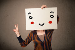 Woman holding a cardboard with a smiley face on it Stock Images