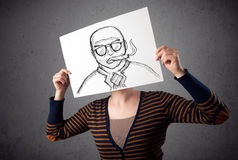 Woman holding a cardboard with a smoking man on it in front of h Royalty Free Stock Images