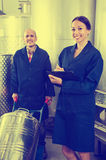 Woman holding cardboard and standing with man working. Glad diligent female winery worker taking notes while male one working in fermentation section Royalty Free Stock Photography