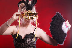 Woman holding carnival mask feather fan in hand Royalty Free Stock Photo