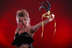 Woman holding carnival mask feather fan in hand Stock Photo