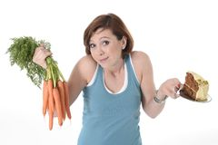 Woman holding carrots and cake healthy nutrition Royalty Free Stock Image
