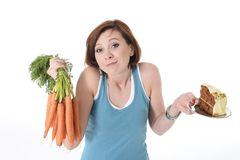 Woman holding carrots and cake healthy nutrition Royalty Free Stock Images