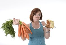 Woman holding carrots and cake healthy nutrition Stock Image