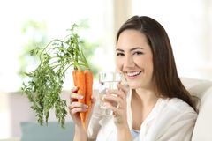 Woman holding carrots and a water glass looking at camera. Happy woman holding carrots and a water glass looking at camera sitting on a couch in the living room Stock Images