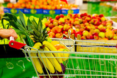 Woman holding cart with fresh fruits and vegetables in shopping centre Stock Photo