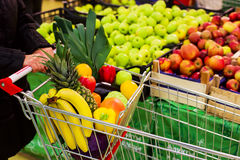 Woman holding cart with fruits and vegetables in shopping centre Stock Images
