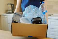 Woman holding a carton with plastic bottles, prepairing for recycling. Woman holding a carton with plastic bottles and containers, prepairing for recycling Royalty Free Stock Images