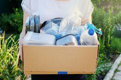 Woman holding a carton with plastic bottles, prepairing for recycling. Woman holding a carton with plastic bottles and containers, prepairing for recycling royalty free stock photo