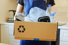Woman holding a carton with plastic bottles, prepairing for recycling. Woman holding a carton with plastic bottles and containers, prepairing for recycling stock photos