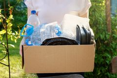 Woman holding a carton with plastic bottles, prepairing for recycling. Woman holding a carton with plastic bottles and containers, prepairing for recycling Stock Photo